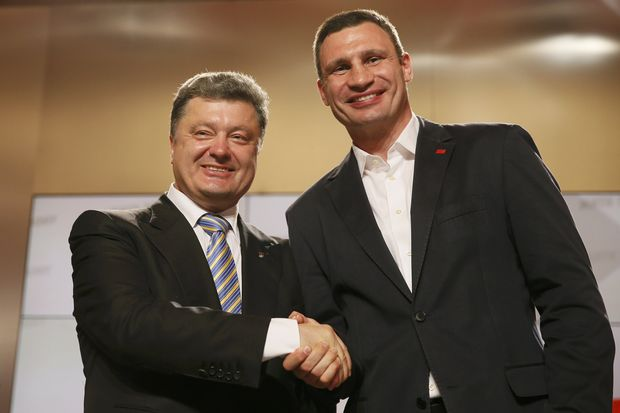 Ukrainian businessman, politician and presidential candidate Poroshenko gestures as heavyweight boxing champion and UDAR  party leader Klitschko looks on during a rally at Poroshenko's election headquarters in Kiev
